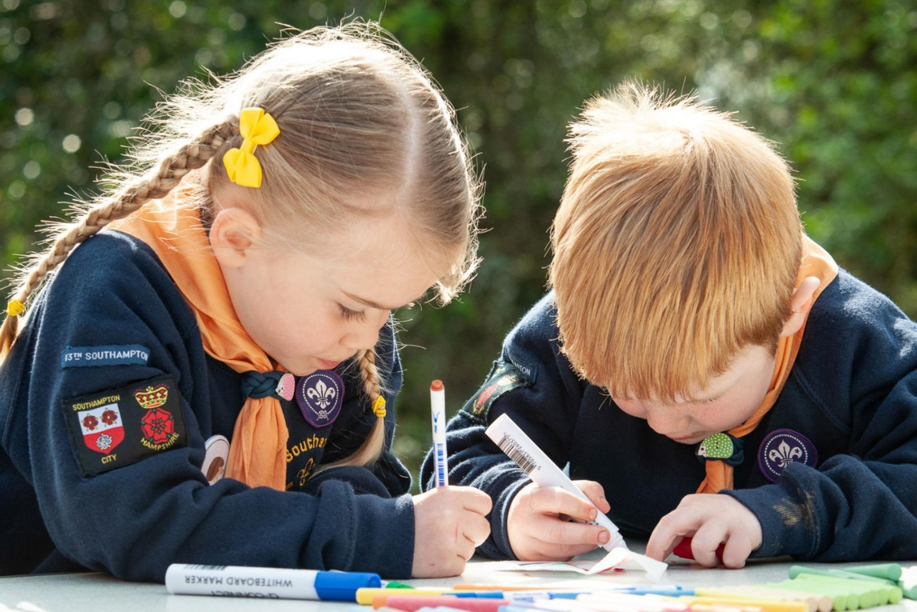 Two children using colouring pens