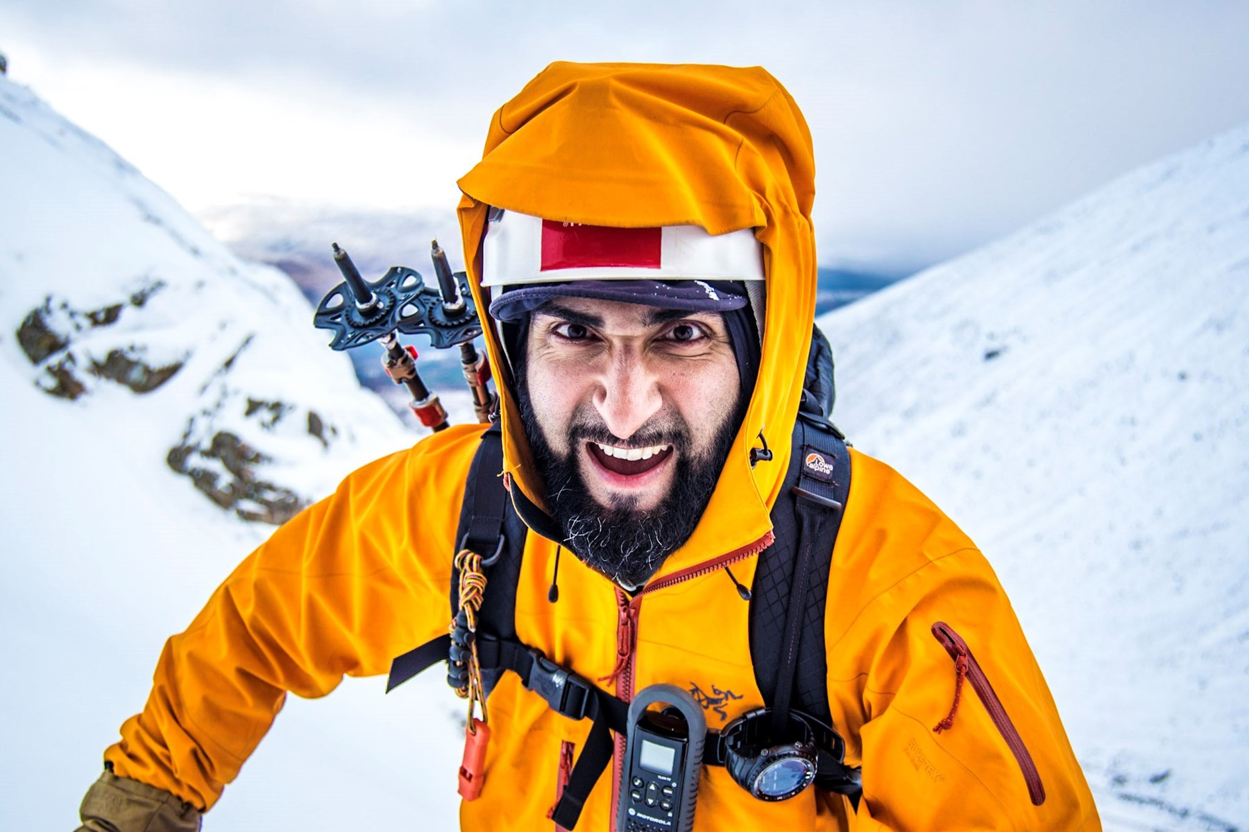 Mahroof smiling nearing a snow peaked summit