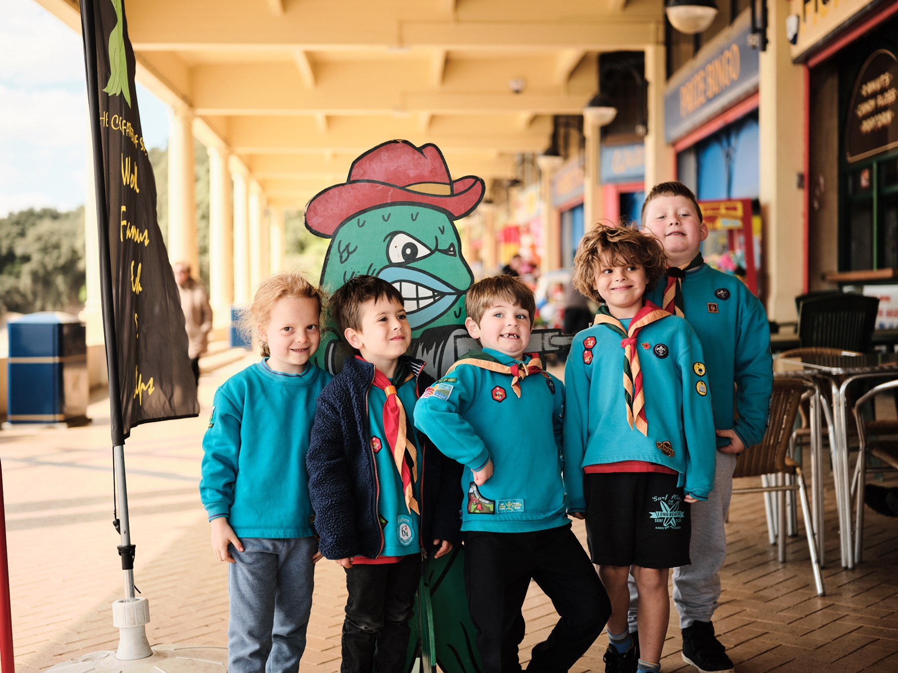 Five Beavers pose with a chip shop mascot for a photo. They're smiling and pulling silly faces at the camera.