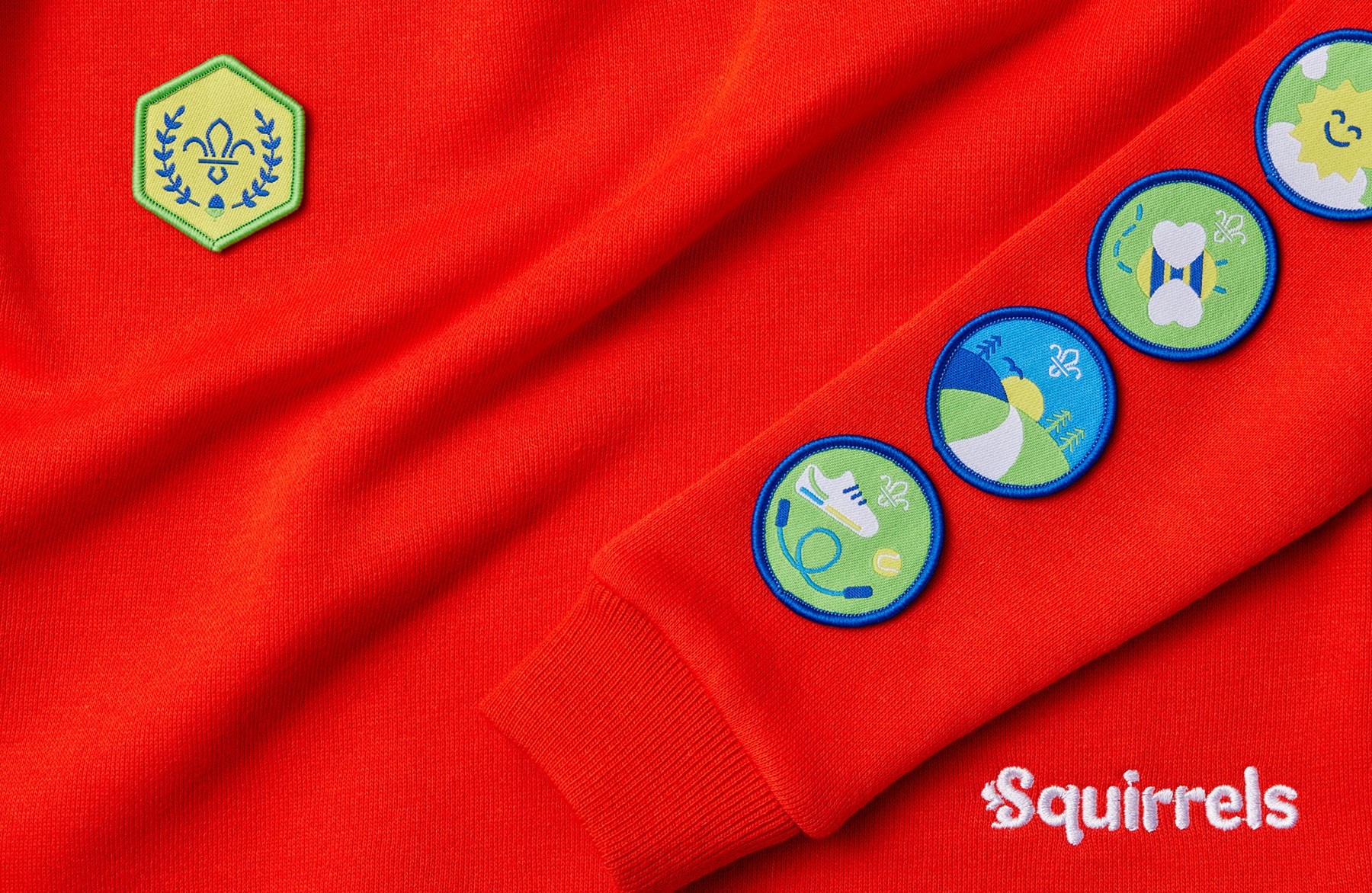 The Be Active, Explore Outdoors, Go Wild and Feel Good Activity Badges along the arm of a red Squirrel Scout jumper, with the Chief Scout's Acorn Award across the heart.
