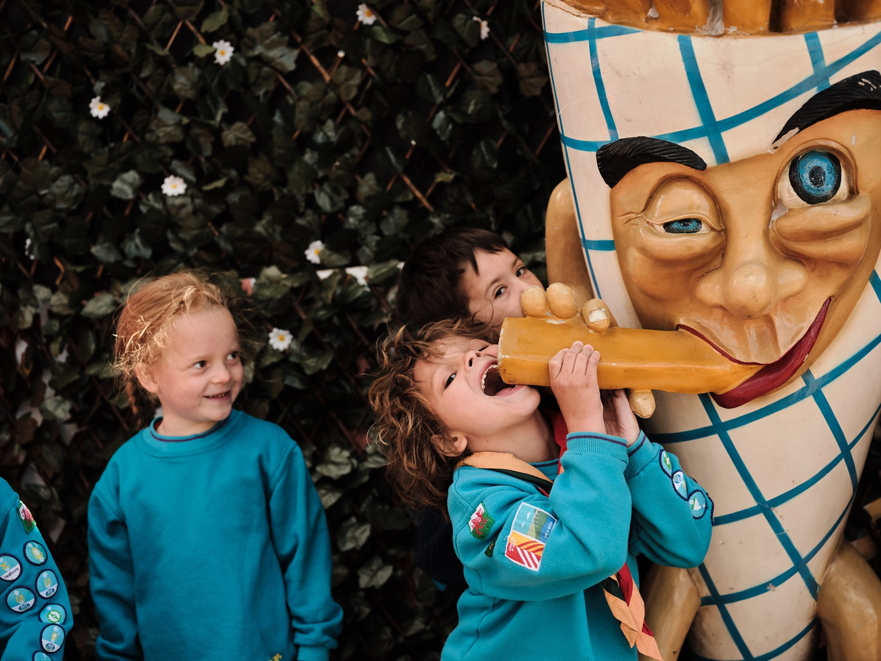 Four Beavers pose for a photo with a statue of a giant cone of chips. One of the Beavers is leaning up on his tip toes with his mouth wide open, pretending to eat the statue.